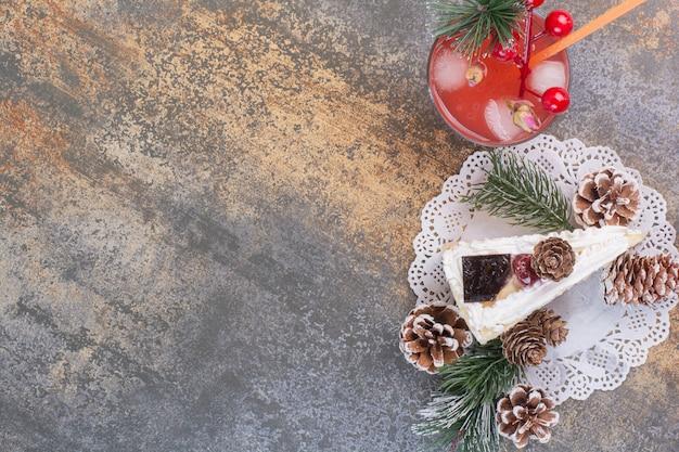 Ein stück kuchen mit tannenzapfen und kaltem erdbeersaft mit stroh.