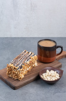 Ein stück kuchen mit tasse aromakaffee auf grauem tisch.