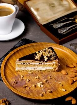 Ein stück kuchen mit vanillecreme-walnüssen und schokoladenglasur