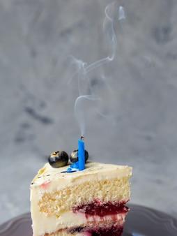 Ein stück kuchen mit weißer sahne und einer erloschenen einzelkerze, urlaubskonzept