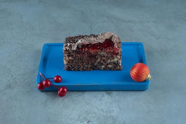 Ein stück kuchen und weihnachtskugeln auf einer platte auf marmoroberfläche