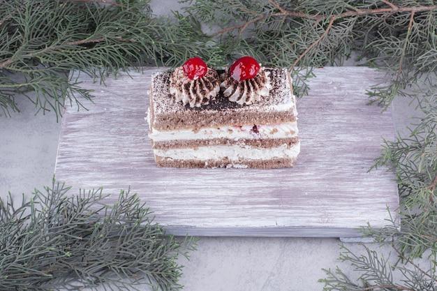 Ein stück leckeren kuchens auf holzbrett.