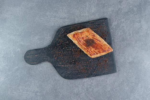 Ein stück leckeren kuchens mit kakaopulver auf einem dunklen brett