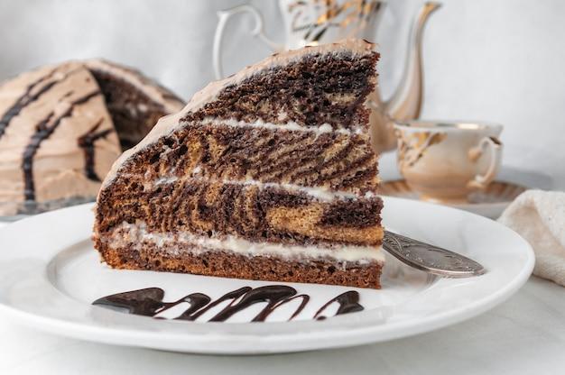 Ein stück marmorkuchen mit sahne garniert mit zuckerguss und schokolade auf einem weißen teller mit einer gabel nahaufnahme