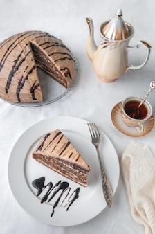 Ein stück marmorkuchen mit sahne. mit zuckerguss und schokolade garniert. auf einem weißen teller mit einer gabel. der hintergrund ist weiß. von oben betrachten. in der nähe einer kaffeekanne, tasse und kuchen.
