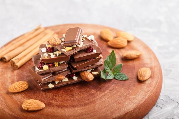 Ein stück milchschokolade mit mandeln und getrockneten früchten auf einem braunen holzbrett auf einer grauen betonoberfläche. seitenansicht