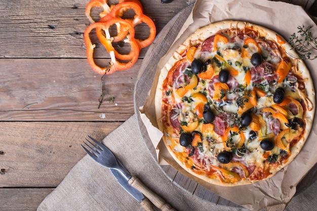 Ein stück peperoni-pizza pflücken. hände, die pizzastück pflücken. draufsicht der leckeren heißen peperoni-pizza auf schwarzem betonhintergrund