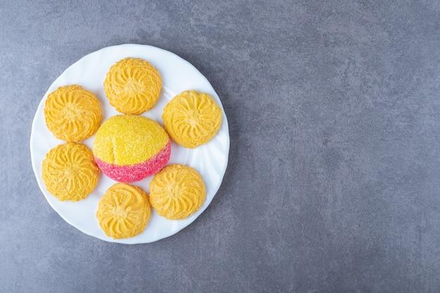 Ein stück pfirsich geformter keks und keks auf einem teller auf marmortisch.