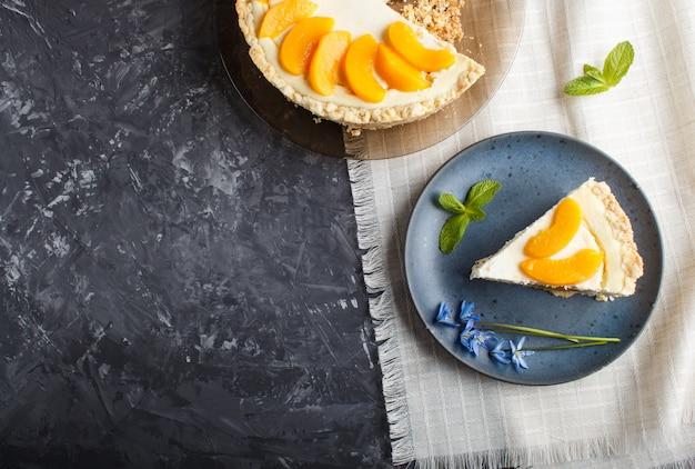 Ein stück pfirsichkäsekuchen auf einer blauen platte mit blauen blumen auf einem schwarzen hintergrund.