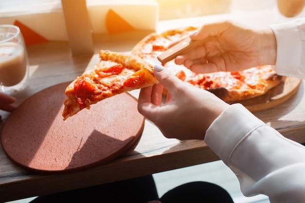 Ein stück pizza in der hand nahaufnahme. pizza steht auf einem tisch in einem café
