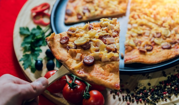 Ein stück pizza in seiner hand. ein restaurant.