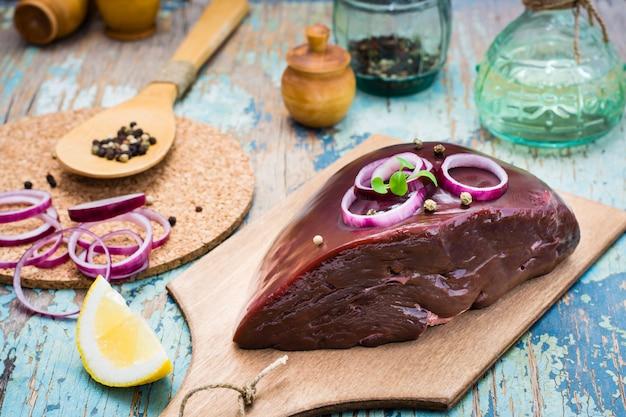Ein stück rohe rindfleischleber auf einem schneidebrett, einer zwiebel, einer zitrone und gewürzen für das kochen auf einem holztisch