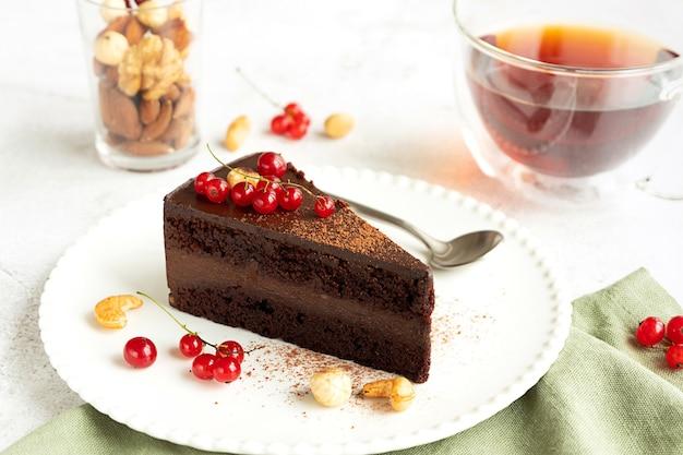 Ein stück roher veganer schokoladen-cashew-kuchen auf einem weißen teller. hellgrauer betonhintergrund, rote johannisbeeren, eine tasse tee und ein glas mit verschiedenen nüssen.
