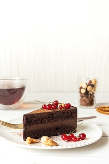 Ein stück roher veganer schokoladen-cashew-kuchen auf einem weißen teller. hellgrauer hintergrund, rote johannisbeeren, eine tasse tee und ein glas mit verschiedenen nüssen. platz kopieren.