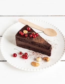 Ein stück roher veganer schokoladen-cashew-kuchen auf einem weißen teller, nahaufnahme. weißer holzhintergrund, holzlöffel, rote johannisbeeren und nüsse.
