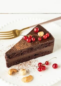 Ein stück roher veganer schokoladen-cashew-kuchen auf einem weißen teller, nahaufnahme. weißer holzhintergrund, rote johannisbeeren und nüsse.