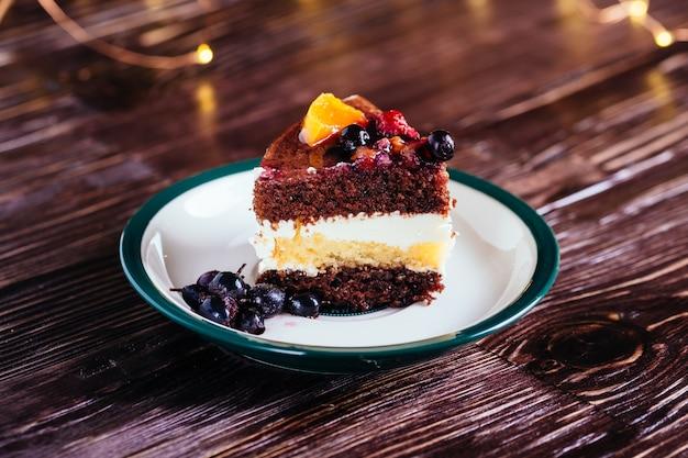 Ein stück schokolade des kuchens trägt süßspeise auf holzoberfläche mit bokeh lichtern früchte