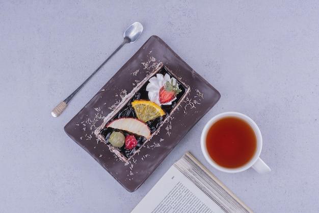 Ein stück schokoladenfruchtkuchen mit einer tasse tee, draufsicht