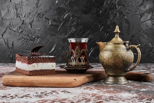 Ein stück schokoladenkäsekuchen mit einem glas tee.