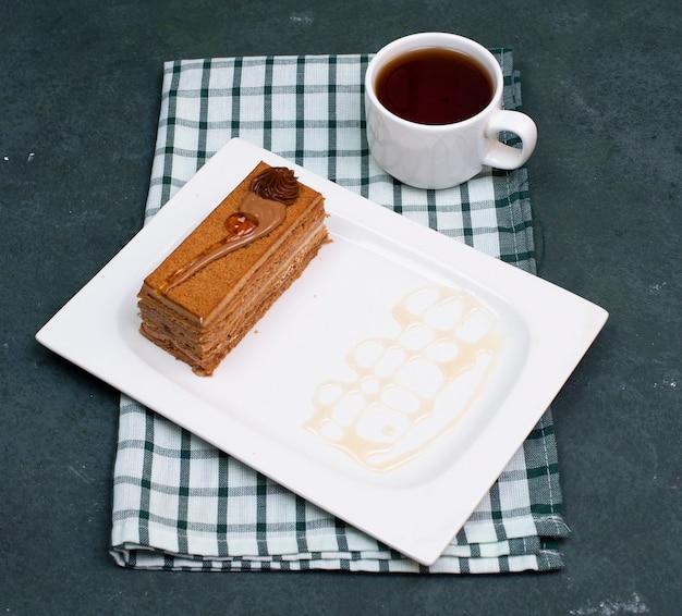 Ein stück schokoladenkakaokuchen mit einer tasse tee. ansicht von oben.