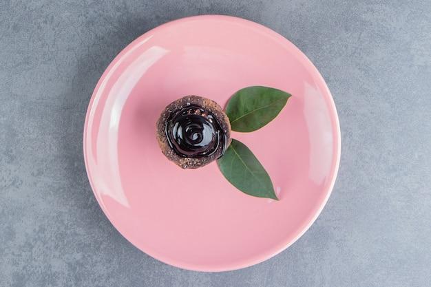 Ein stück schokoladenkuchen mit blättern auf einem rosa teller