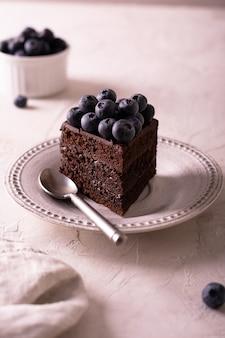 Ein stück schokoladenkuchen mit blaubeere auf einem weißen teller