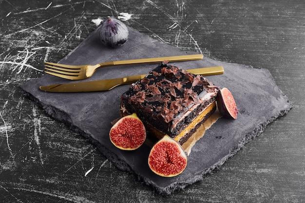 Ein stück schokoladenkuchen mit feigen auf einer steinplatte.