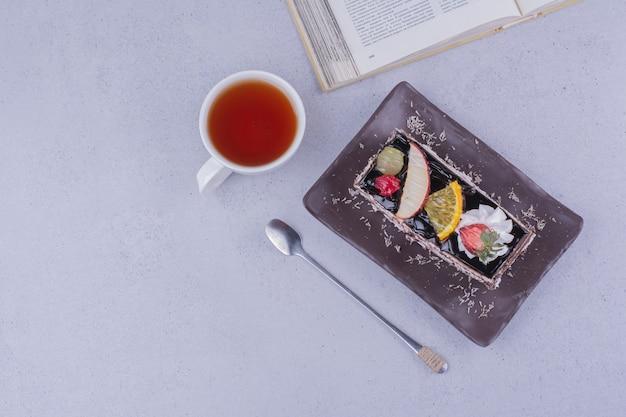 Ein stück schokoladenkuchen mit früchten und einer tasse getränk.