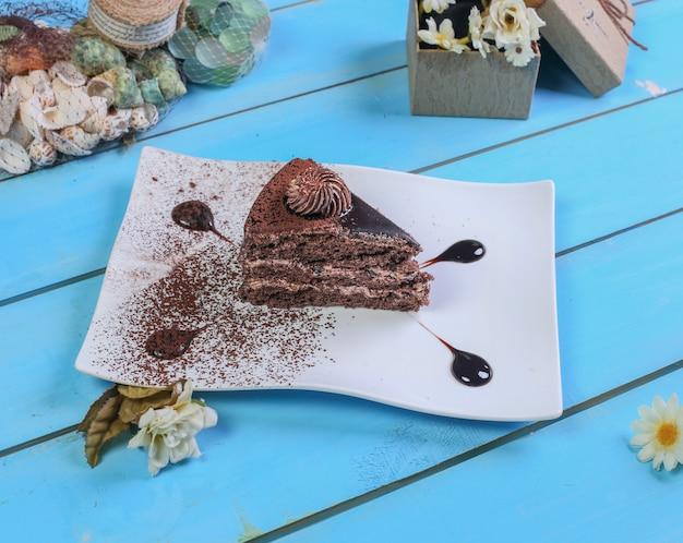 Ein stück schokoladenkuchen mit kakaopulver.