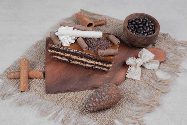 Ein stück schokoladenkuchen, zimt und tannenzapfen auf sackleinen. hochwertiges foto