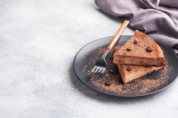 Ein stück schokoladenquarkauflauf auf einem teller, ein stück kuchen mit schokolade und kaffee.,