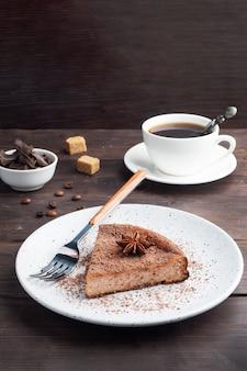 Ein stück schokoladenquarkauflauf auf einem teller, eine portion kuchen mit schokolade und kaffee. dunkler rustikaler hölzerner hintergrund. speicherplatz kopieren