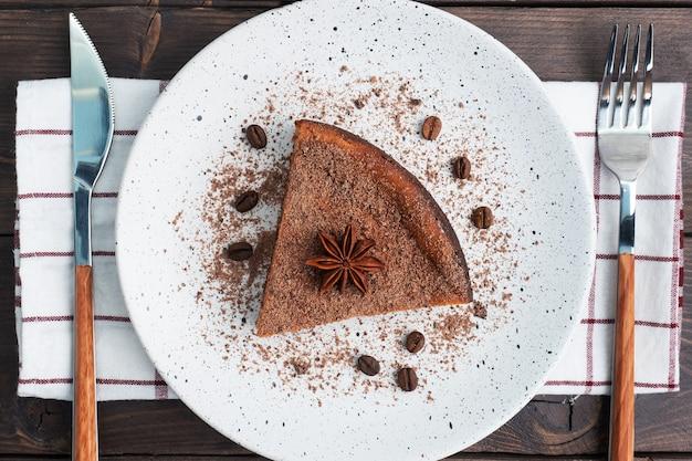 Ein stück schokoladenquarkauflauf auf einem teller, eine portion kuchen mit schokolade und kaffee. dunkles holz rustikal. draufsicht