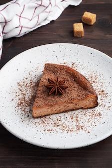 Ein stück schokoladenquarkauflauf auf einem teller, eine portion kuchen mit schokolade und kaffee. dunkles holz rustikal.