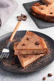 Ein stück schokoladenquarkauflauf auf einem teller, eine portion kuchen mit schokolade und kaffee.