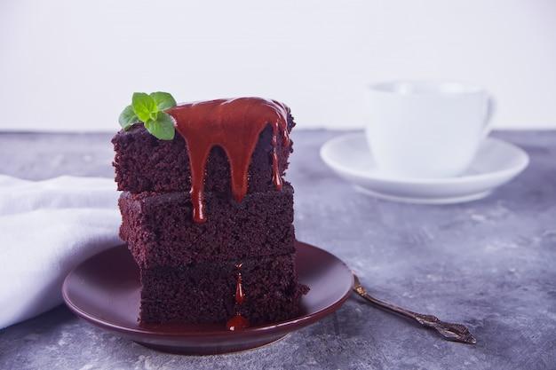 Ein stück selbst gemachter schokoladenkuchen auf der platte mit zuckerglasur, tadellosem blatt und tasse tee
