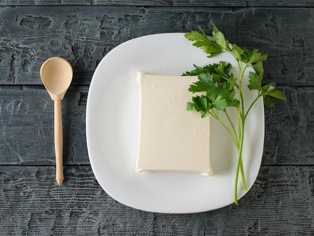 Ein stück serbischer käse mit petersilie und einem holzlöffel auf einem schwarzen tisch. der blick von oben. milchprodukt.