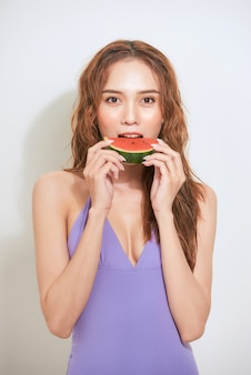 Ein stück sommergüte. schöne junge frau, die scheibe wassermelone hält und lächelt