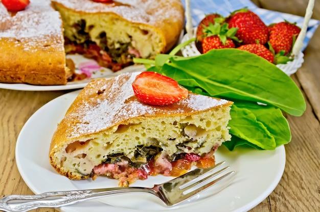 Ein stück süße torte mit erdbeeren und sauerampfer, serviette, torte, gabel auf dem hintergrund von holzbrettern