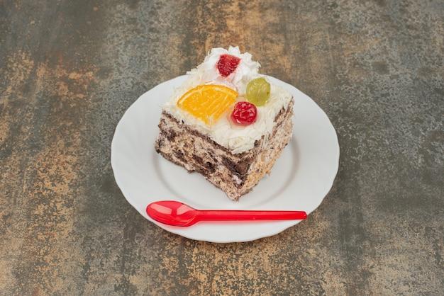 Ein stück süßer kuchen mit rotem löffel auf weißem teller