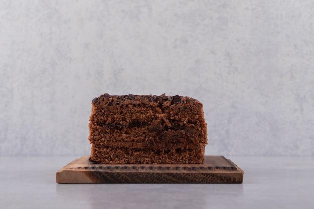 Ein stück süßer schokoladenkuchen auf steintisch gelegt.
