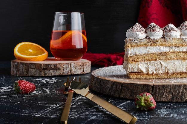 Ein stück tiramisu-kuchen mit einem glas limonade.