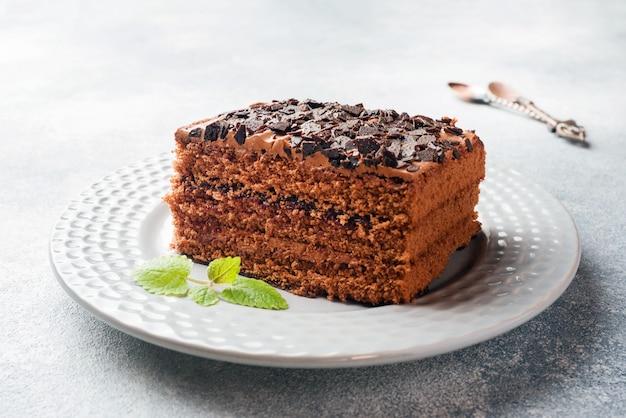 Ein stück trüffelkuchen mit schokolade auf einem grauen konkreten hintergrund.