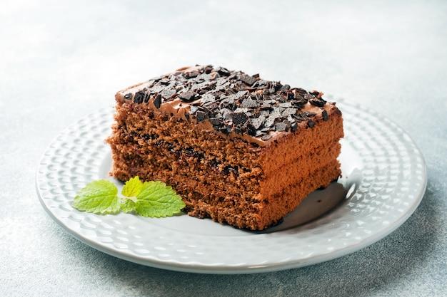 Ein stück trüffelkuchen mit schokolade auf grauem beton.