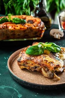 Ein stück vegetarische lasagne mit pilzen, tomaten und basilikum auf dem vertikalen foto der platte.