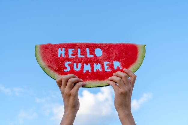 Ein stück wassermelone vor blauem himmel. kinderhände halten eine scheibe wassermelone mit dem text hallo sommer. sommerzeit-konzept.