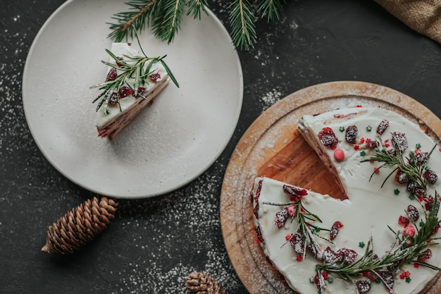 Ein stück weihnachtskuchen auf einem weißen teller vor dem hintergrund von tannenzweigen und girlanden.