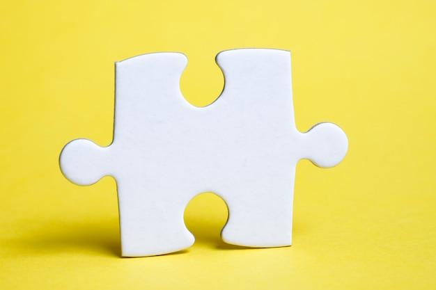 Ein stück weißes puzzlespiel auf einer gelben wand. das konzept der notwendigen details für die aufgabe.