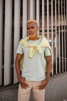 Ein stylischer junger mann mit gefärbtem bart posiert für die kamera