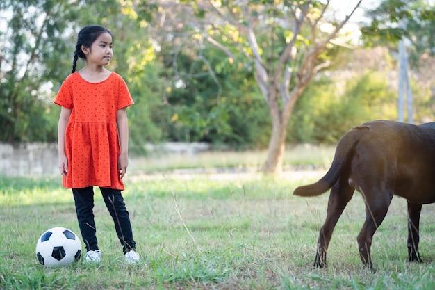 Ein südostasiatisches kindermädchen mit fußball mit ihrem großen schwarzen hund außerhalb des grasbodens im hinterhof am abend. konzept für tierliebhaber